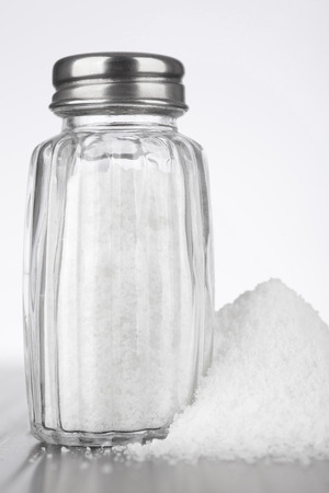 shaker: glass salt shaker on gray table and white background Stock Photo
