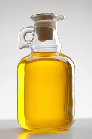 glass bottle of oil on white background