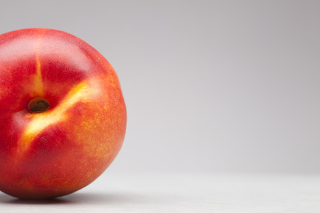 closeup of red and yellow peach or nectarine on white background with blank space for text