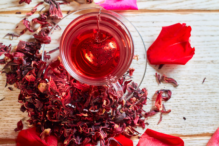 Red Hot Hibiscus tea in a glass mug on a wooden table among rose petals and dry tea custard with metallic heart Standard-Bild