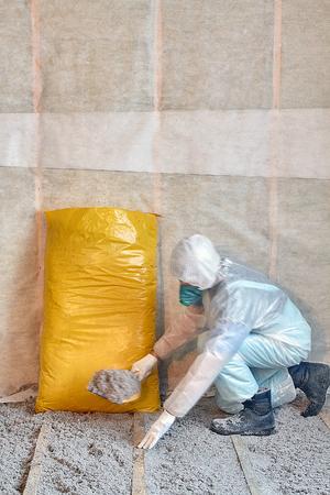 celulosa: Maestro aislamiento de celulosa apiladas en el suelo, suelo de aislamiento, un hogar cálido, aislamiento ecológico, papel de aislamiento, constructor en el trabajo