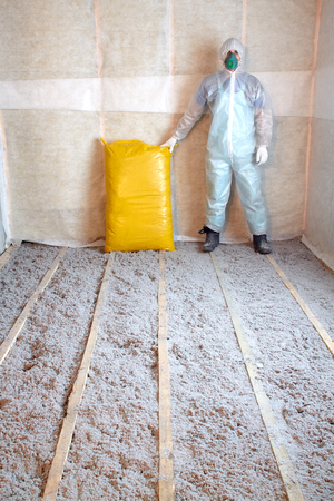 Work composed of cellulose insulation in the floor, floor heating, warm house, eco-friendly insulation, insulation paper, a builder at work Standard-Bild