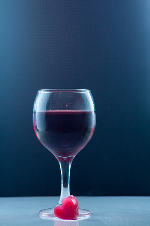 Glass of red Fina in a glass isolated on background with a romantic heart ice
