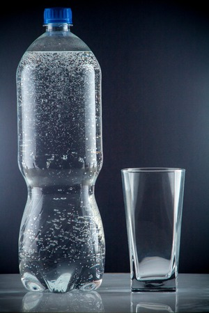 bottle of clear drinking cold mineral water with gas in isolation on the background next to a glass transparent glass Stock Photo