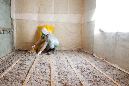 Het werk bestaat uit cellulose-isolatie in de vloer, vloerverwarming isolatie, warm huis, eco-vriendelijke isolatie, isolatie papier, een bouwer op het werk Stockfoto