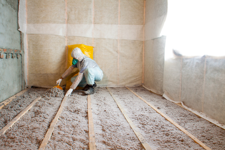 attic: Work composed of cellulose insulation in the floor, floor heating insulation , warm house, eco-friendly insulation, insulation paper, a builder at work Stock Photo