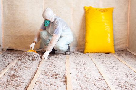 Arbeit aus Zellstoff-Isolierung in den Boden, Fußbodenheizung Isolierung, warmes Haus, umweltfreundliche Isolierung, Isolierpapier, ein Baumeister bei der Arbeit