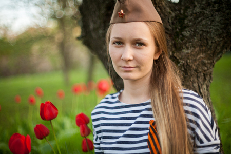 Girl in the cap on May 9, the day of victory in the colors of red tulips on a green strive in the forest