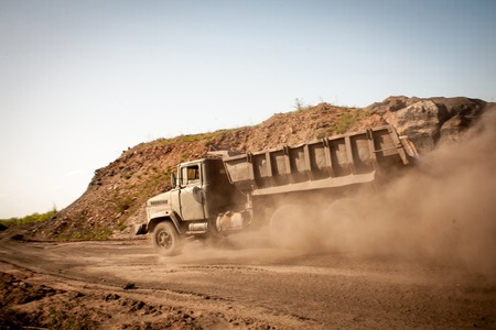 mine site: Truck carries a load in the quarry full body of rubble and building material of soil in the dust
