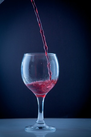 bright beautiful red wine pouring jet into a transparent glass cup isolated on a wite background Stock Photo