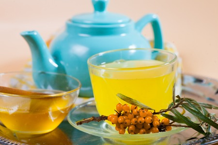 argousier: Tea made from sea buckthorn berries healthy for health delicious, saturated with vitamins surrounded by berries and sea buckthorn leaves for family tea drinking and maintaining health in the body