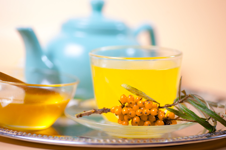 Tea made from sea buckthorn berries healthy for health delicious, saturated with vitamins surrounded by berries and sea buckthorn leaves for family tea drinking and maintaining health in the body