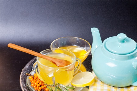 Healing sea-buckthorn tea delicious aromatic full of vitamin and microelements of bright yellow color with berries and leaves of the tea with sea-buckthorn on a black background. Stock Photo