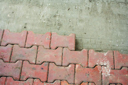 Laying Paving Slabs by mosaic close-up. Repairing sidewalk. Workers laying stone paving slab. laying of paving slabs by a professional master builder in blue overalls Stock Photo