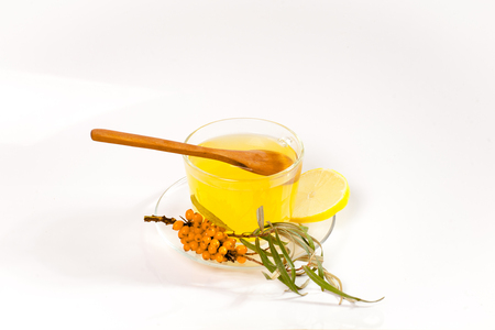 argousier: Healing sea-buckthorn tea delicious aromatic full of vitamin and microelements of bright yellow color with berries and leaves of the sea buckthorn fruit on a white background.