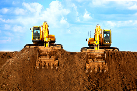 Two excavators dig the ground at the construction site