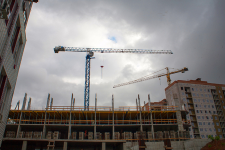 Tower cranes against the evening sky. House under construction. Industrial skyline with houses under construction and tower cranes against the background of industrial landscape