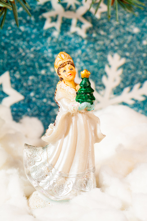 New Years background on a background of a New Year tree Snow Maiden toy holds a New Years green fir in hands on snow... Stock Photo