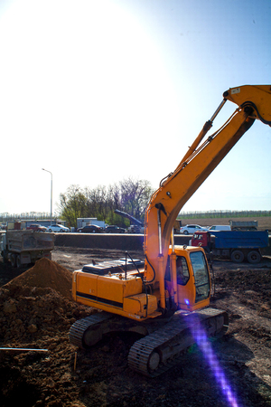 A large construction excavator of yellow color on the construction site in a quarry for quarrying Stock Photo
