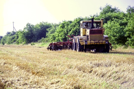 big old Tractor preparing land for sowing. Farmer in tractor preparing land with seedbed cultivator