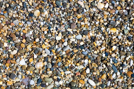 Sea pebbles small rounded stones of different colors on the shore of the ocean beach background