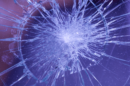 broken glass of a car with cracks in a circle