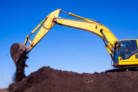 Construction mechanical excavator with a large hydraulic bucket works on the construction site digging a trench and pouring out the soil