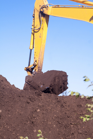 A large metal excavator bucket digs the ground. Parts of construction earthmoving equipment close-up. Digging and filling the soil with an excavator bucket. Stok Fotoğraf