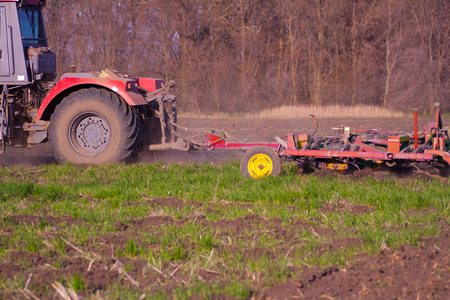 Big Tractor preparing land with seedbed cultivator as part of pre seeding activities in early spring season of agricultural works at farmlands.