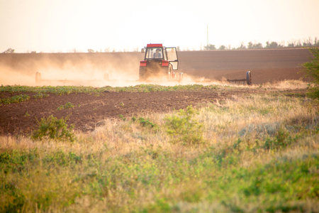 Sowing and plowing action in the spring season Agricultural work with the land in the field for harvest. The work of the tractor farmer on the tractor.
