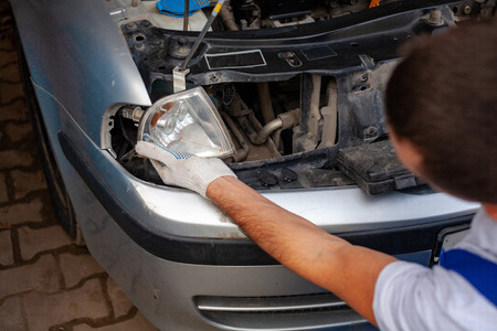 mechanic men with wrench repairing car engine at workshop - auto service, repair, maintenance and people concept. the master repairs the headlight of the car removes the lights 版權商用圖片