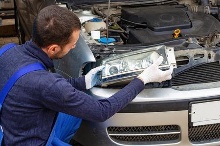 Mechaniker mit Schraubenschlüssel reparieren Automotor in der Werkstatt - Autoservice, Reparatur, Wartung und Menschenkonzept.