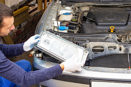 Mechanic in autoservice installing a headlamp to a car. car headlight repair. background image for auto service article.