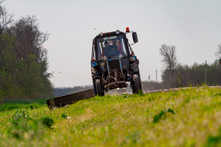 Tractor with a mechanical mower mowing grass on the side of the asphalt road. Road services are engaged in landscaping around roads.