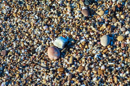 sea pebbles colored granite on the beach background stones. The shore of the beach with sand and pebbles washed by the waves of the sea. Imagens - 129995568