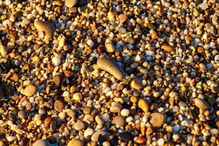 sea pebbles colored granite on the beach background stones. The shore of the beach with sand and pebbles washed by the waves of the sea. Imagens - 129995569