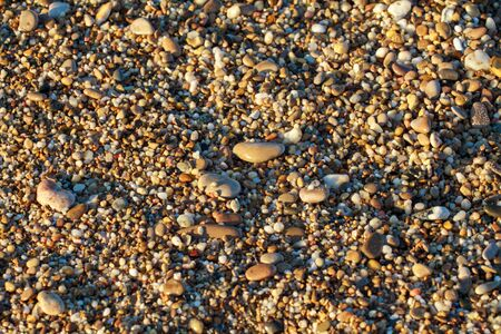 sea pebbles colored granite on the beach background stones. The shore of the beach with sand and pebbles washed by the waves of the sea. Imagens - 129995570