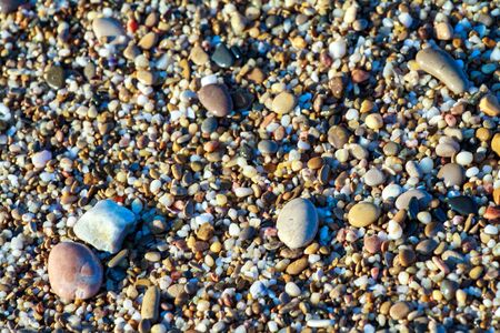 sea pebbles colored granite on the beach background stones. The shore of the beach with sand and pebbles washed by the waves of the sea. Imagens - 129995443