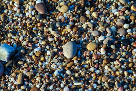sea pebbles colored granite on the beach background stones. The shore of the beach with sand and pebbles washed by the waves of the sea. Imagens - 129995444