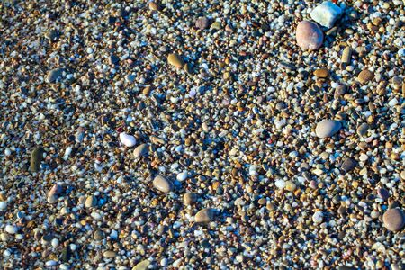 sea pebbles colored granite on the beach background stones. The shore of the beach with sand and pebbles washed by the waves of the sea. Imagens - 129995323