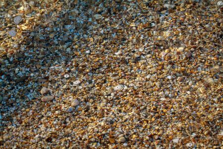 sea pebbles colored granite on the beach background stones. The shore of the beach with sand and pebbles washed by the waves of the sea. Imagens - 129995331