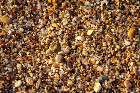 sea pebbles colored granite on the beach background stones. The shore of the beach with sand and pebbles washed by the waves of the sea. Imagens - 129995332
