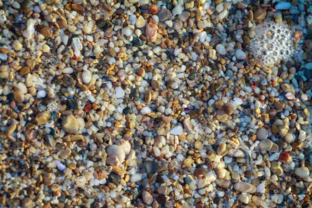 sea pebbles colored granite on the beach background stones. The shore of the beach with sand and pebbles washed by the waves of the sea. Imagens - 131203925