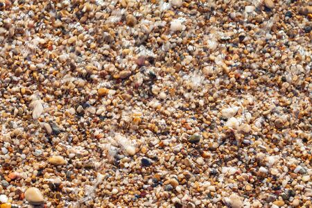 sea pebbles colored granite on the beach background stones. The shore of the beach with sand and pebbles washed by the waves of the sea. Imagens - 131204466