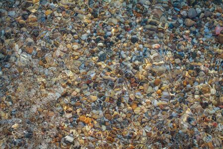 sea pebbles colored granite on the beach background stones. The shore of the beach with sand and pebbles washed by the waves of the sea. Imagens - 131204618