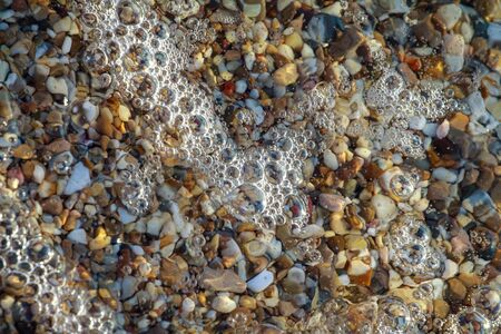 sea pebbles colored granite on the beach background stones. The shore of the beach with sand and pebbles washed by the waves of the sea. Imagens - 131204665