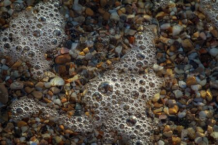 sea pebbles colored granite on the beach background stones. The shore of the beach with sand and pebbles washed by the waves of the sea. Imagens - 131204920