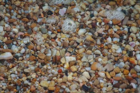 sea pebbles colored granite on the beach background stones. The shore of the beach with sand and pebbles washed by the waves of the sea. Imagens - 131204365