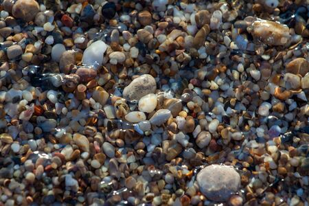 sea pebbles colored granite on the beach background stones. The shore of the beach with sand and pebbles washed by the waves of the sea. Imagens - 131204281