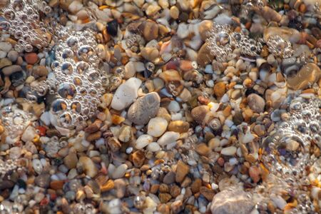 sea pebbles colored granite on the beach background stones. The shore of the beach with sand and pebbles washed by the waves of the sea. Imagens - 131204546